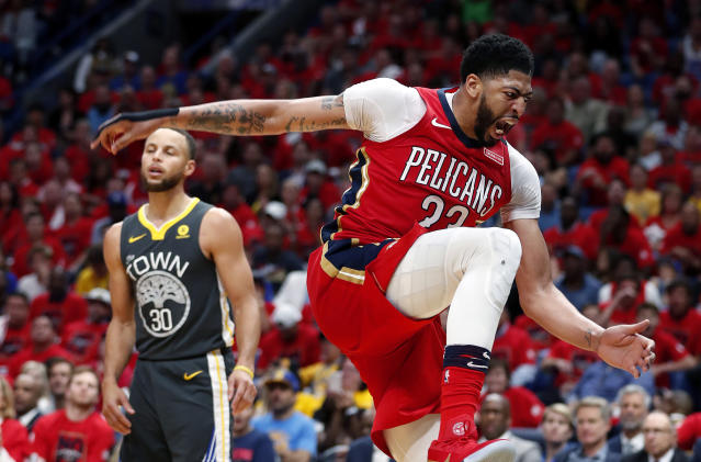Anthony Davis roars after a monster slam dunk during Friday's Game 3, and Stephen Curry can't do much about it. (AP)