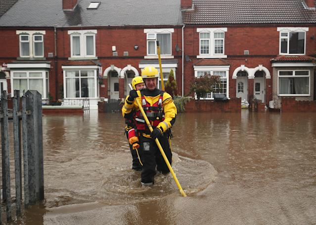Fire and Rescue service members walk through flood water to rescue residents in Doncaster, Yorkshire, as parts of England endured a month's worth of rain in 24 hours, with scores of people rescued or forced to evacuate their homes, others stranded overnight in a shopping centre, and travel plans thrown into chaos.