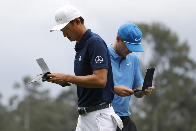 Li Haotong of China (L) and Russell Henley of the U.S. look over their notes before hitting off the 4th tee during third round play of the 2018 Masters golf tournament at the Augusta National Golf Club in Augusta, Georgia, U.S. April 7, 2018. REUTERS/Jonathan Ernst