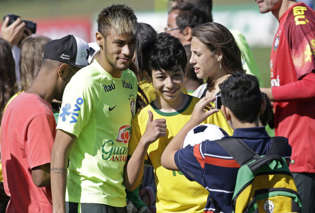 Brazil's Neymar poses for pictures with fans prior to a training session in Teresopolis, Brazil, Wednesday, June 25, 2014. About fifty children that were victims of floods and landslides in Rio de Janeiro state in 2011 watched the training. Brazil will face Chile on June 28 in the round of 16 of the 2014 soccer World Cup. (AP Photo/Andre Penner)