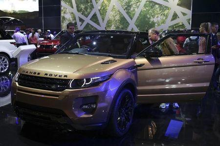 A visitor stands next to the Range Rover Evoque during a media preview day of the Johannesburg International Motor Show