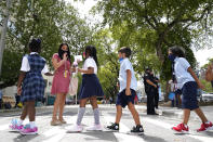 Teacher Vanessa Rosario greets students outside of iPrep Academy on the first day of school, Monday, Aug. 23, 2021, in Miami. Schools in Miami-Dade County opened Monday with a strict mask mandate to guard against coronavirus infections. (AP Photo/Lynne Sladky)
