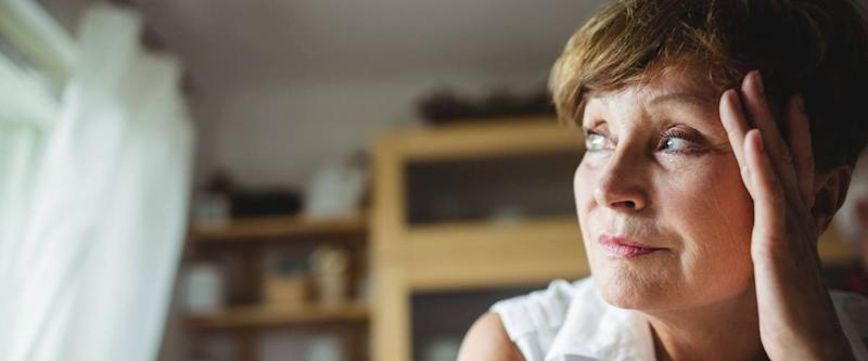 Worried senior woman with hand on forehead at home