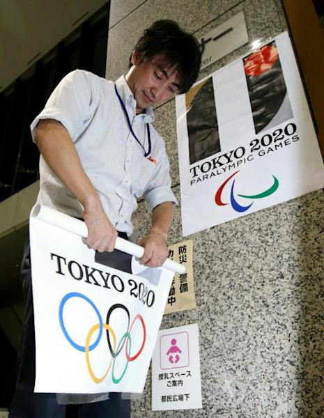 Posters bearing the original logo of the Tokyo 2020 Olympic Games are removed from Tokyo City Hall after the emblem was scrapped in an embarrassing plagiarism scandal