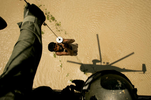<p>A villager is rescued by a Pakistani navy helicopter from a flooded area of Ghaus Pur near Sukkur, in Pakistan's Sindh province, Aug. 11, 2010. (AP Photo/Shakil Adil) </p>