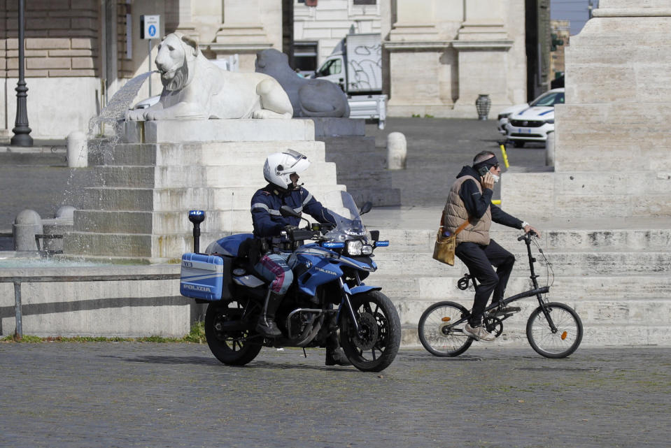 A Police officer patrols Rome's central Piazza del Popolo, Saturday, April 3, 2021. Italy went into lockdown on Easter weekend in its effort to battle then Covid-19 pandemic. (AP Photo/Gregorio Borgia)