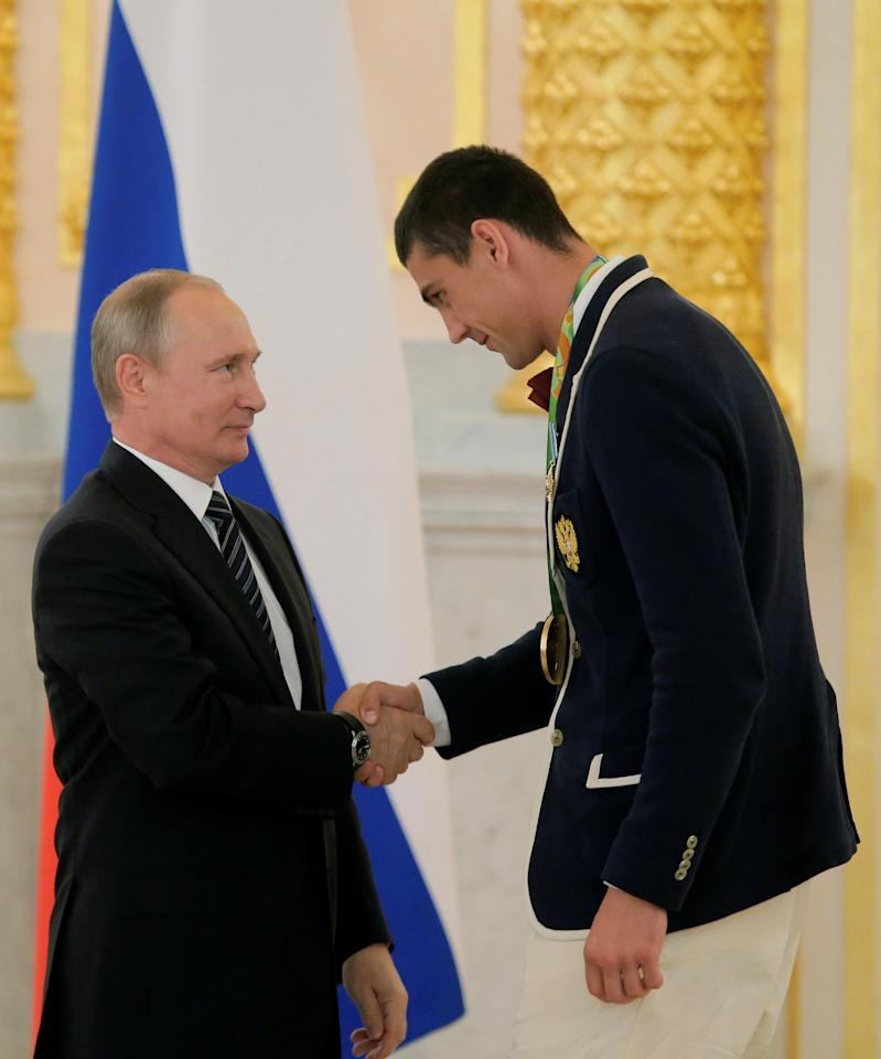 Russian President Vladimir Putin awards boxer Evgeny Tishchenko during a ceremony for Russian Olympic medallists returning home from the 2016 Rio Olympics, at the Kremlin in Moscow, Russia August 25, 2016. REUTERS/Maxim Shemetov