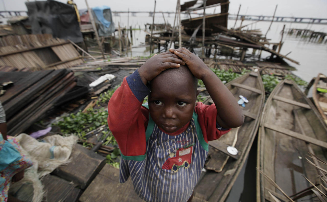 In this photo taken Thursday, July 26, 2012, a child stand in front of his demolished stilt house at Makoko in Lagos, Nigeria. The teeming, floating Makoko slum rises out of the murky lagoon water that separates mainland Nigeria from the island that gave birth to its largest city, a permanent haze of smoke rising from its homes built on timber stilts. A government-led eviction last week that saw men in speedboats destroy homes with machetes there left about 3,000 people homeless and raised new fears among activists that authorities may try to wipe it out the area entirely. (AP Photo/Sunday Alamba)
