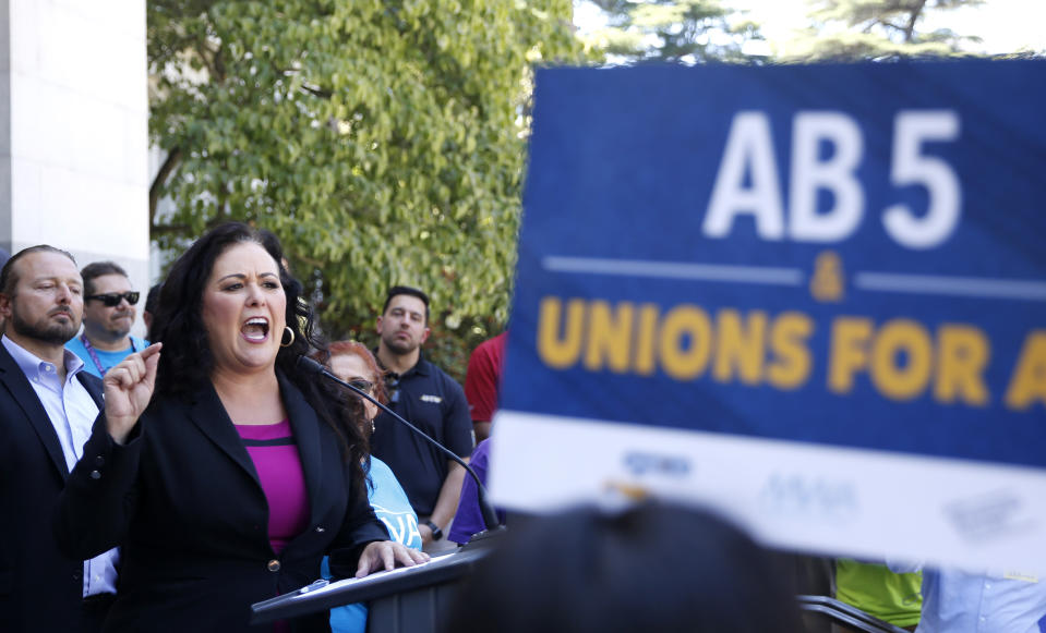 Assemblywoman Lorena Gonzalez, D-San Diego, speaks at a rally after her measure to limit when companies can label workers as independent contractors was approved by a Senate committee, in Sacramento, Calif., Wednesday, July 10, 2019. The measure, AB5, is aimed at major employers like Uber and Lyft. (AP Photo/Rich Pedroncelli)