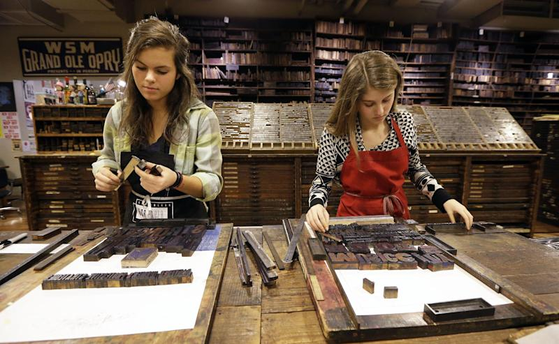 This Jan. 15, 2014 photo shows Lydia Witty, left, and Laura Baisden setting type at Hatch Show Print in Nashville, Tenn. There's no cost to watch the presses and the staff churn out the iconic handmade art that has been used by everyone from Grand Ole Opry stars to blues and jazz greats and modern rock bands. If you want to take some posters home, there is a large selection to choose from. (AP Photo/Mark Humphrey)