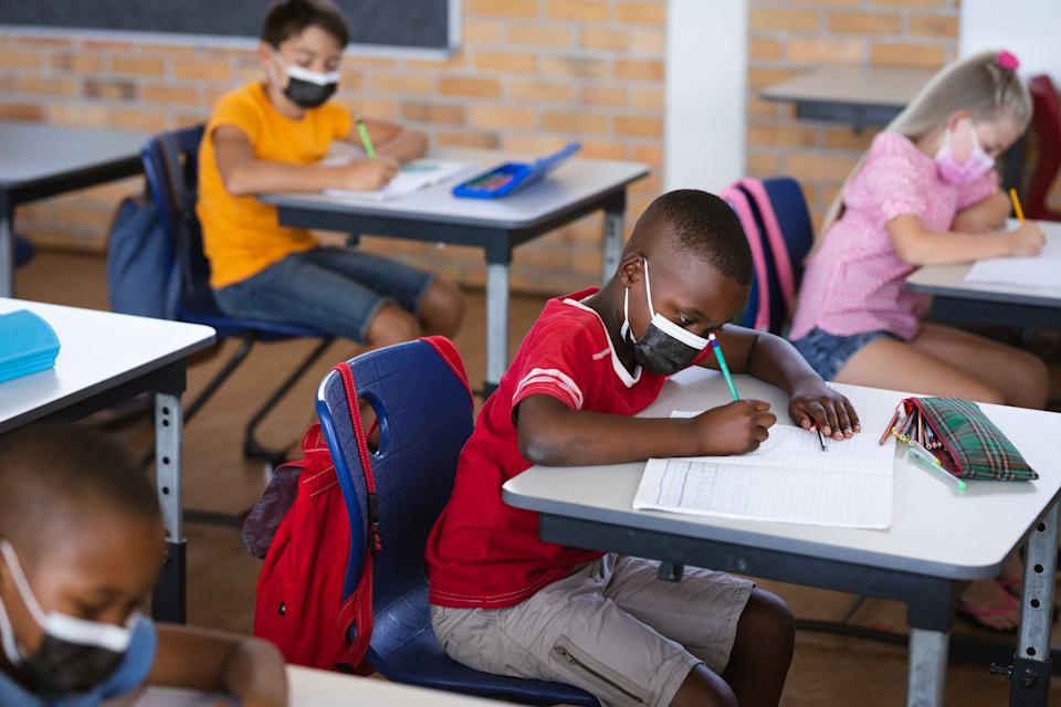 African American boy wearing face mask studying while sitting on his desk in the class at school. The CDC guidance recommended that everyone in K-12 schools wear a mask indoors.