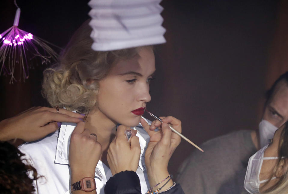 Model Michaela Tomanova has her makeup retouched during the shoot for Julien Fournie's Haute Couture Spring/Summer 2021 fashion collection for a digital presentation of the fashion week, in Paris, Thursday, Jan. 7, 2021. With shows taking place behind closed doors due to the virus pandemic, some designers such as Julien Fournie are becoming versatile: Getting their designs out to the public by making a film of their collection and streaming it online. (AP Photo/Francois Mori)