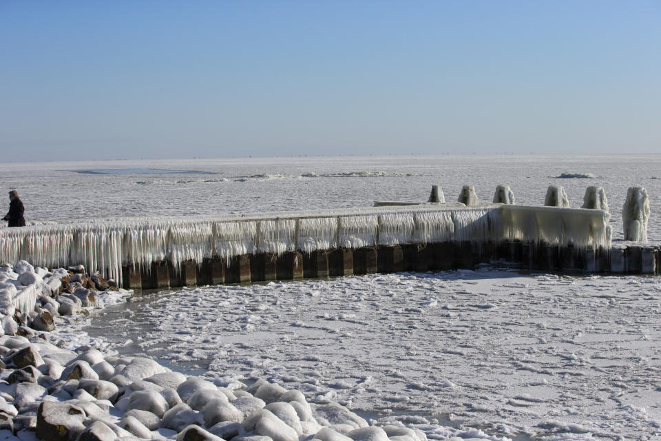 A woman takes pictures of icicles on a jetty at the Afsluitdijk, a dike separating IJsselmeer inland sea, rear, and the Wadden Sea, Netherlands, Thursday, Feb. 11, 2021. The deep freeze gripping parts of Europe served up fun and frustration with heavy snow cutting power to some 37,000 homes in central Slovakia. (AP Photo/Peter Dejong)