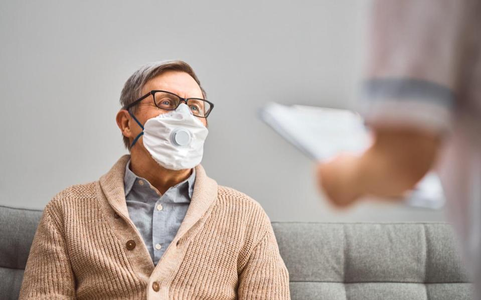 Doctor and senior man wearing face masks during coronavirus and flu outbreak