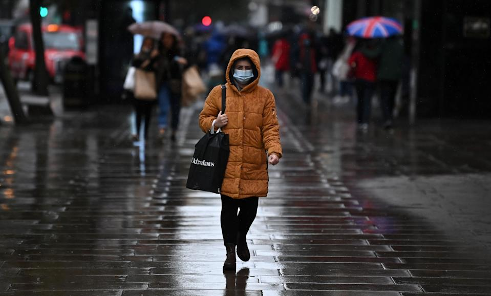 "A pedestrian wearing a face mask or covering due to the COVID-19 pandemic, walks in the rain on Oxford Street in London on October 13, 2020, following the announcement of a new three-tiered system categorising areas of England by rates of coronavirus infection. - The British government on Tuesday insisted it is still ""guided by science"" following criticism that senior ministers had ignored the advice of experts three weeks ago for tougher restrictions to cut rising coronavirus infections. (Photo by DANIEL LEAL-OLIVAS / AFP) (Photo by DANIEL LEAL-OLIVAS/AFP via Getty Images)"