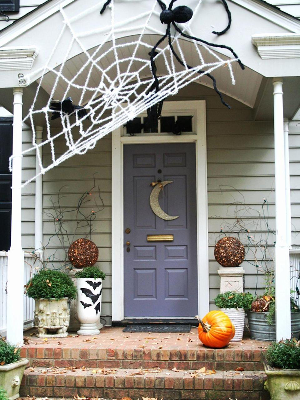 """<p>Craft an oversize spiderweb above your front porch with <a href=""""http://www.instructables.com/id/Gigantic-Halloween-Spider-Web/"""" rel=""""nofollow noopener"""" target=""""_blank"""" data-ylk=""""slk:clothesline style rope"""" class=""""link rapid-noclick-resp"""">clothesline style rope</a> or by simply tying together strands of white Christmas tinsel garland. Don't have great DIY skills? Buy a giant spiderweb for your home on Etsy. </p>"""
