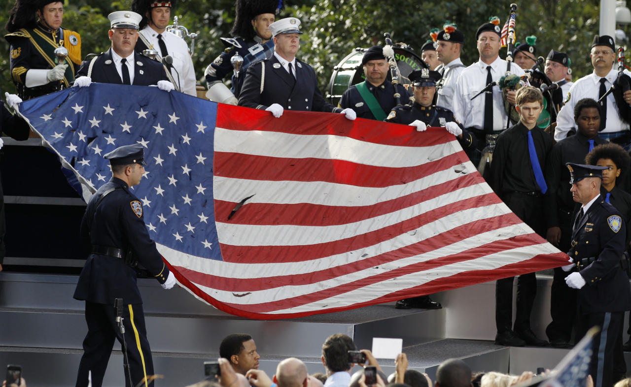 New York City firefighters and police officers hold a damaged flag from the World Trade Center site during ceremonies marking the 10th anniversary of the 9/11 attacks on the World Trade Center, in New York September 11, 2011. (REUTERS/Larry Downing)