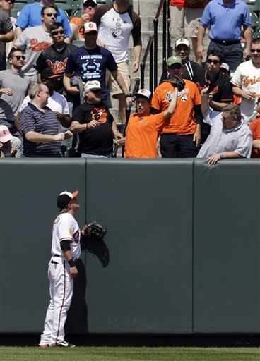 Baltimore Orioles left fielder Nate McLouth looks on as a fan catches a solo home run by Toronto Blue Jays' Rajai Davis in the third inning of a baseball game on Wednesday, April 24, 2013, in Baltimore. (AP Photo/Patrick Semansky)