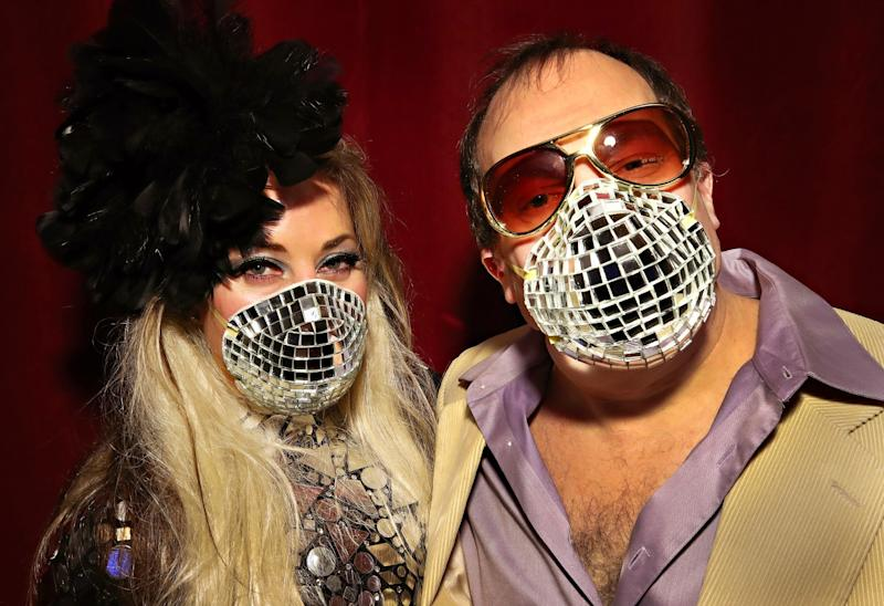 "UNITED STATES: Allison Eden and Gary Goldenstein wear disco-ball-inspired masks during the opening of the ""Studio 54: Night Magic"" exhibit at the Brooklyn Museum in New York."