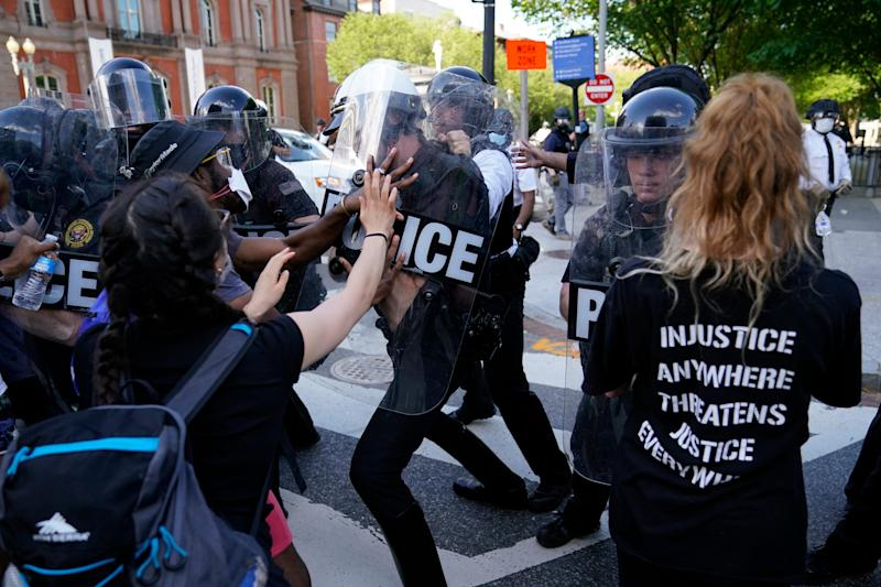Demonstrators clash with police as they protest the death of George Floyd, Saturday, May 30, 2020, near the White House in Washington.