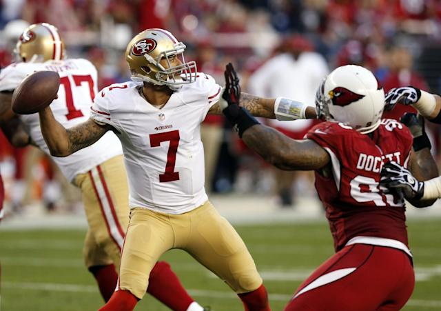 San Francisco 49ers quarterback Colin Kaepernick (7) throws under pressure from Arizona Cardinals defensive end Darnell Dockett (90) during the second half of an NFL football game, Sunday, Dec. 29, 2013, in Glendale, Ariz. The 49ers won 23-20. (AP Photo/Ross D. Franklin)