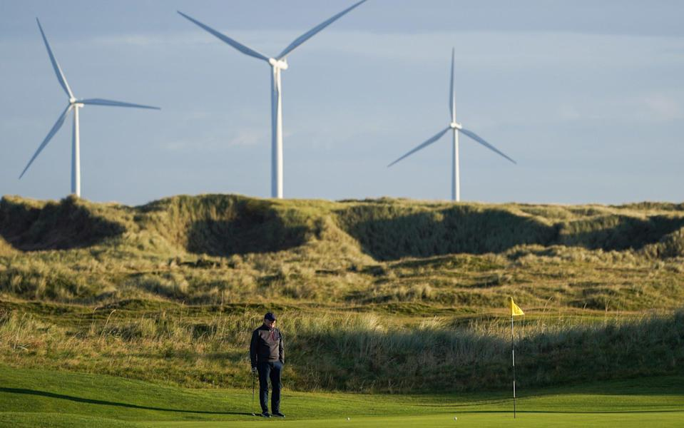 The EDF energy offshore wind farm on Teesside is seen in the distance as golfers play at Redcar golf club - Ian Forsyth/Getty Images Europe