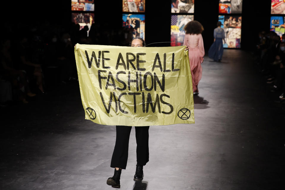 An activist displays a banner during Dior's Spring-Summer 2021 fashion collection presented Tuesday, Sept. 29, 2020 during the Paris fashion week. (AP Photo/Francois Mori)