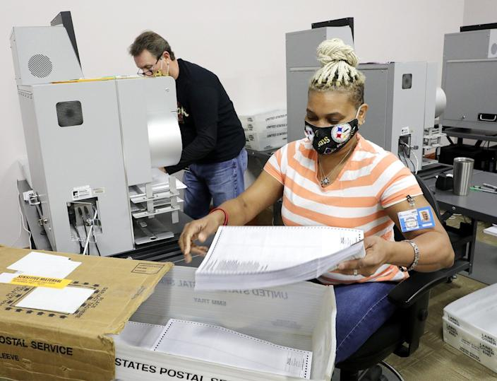 Absentee ballot clerk Katrina McReynolds, right, collects absentee ballots that Gene Shell, left, had just scanned in a ballot scanner at the Franklin County Board of Elections, 1700 Morse Road on Tuesday, April 21, 2020. The ballots were only scanned; they will not be tabulated until Tuesday.