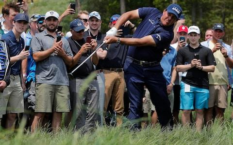 Phil Mickelson draws the eyes and cameraphones of the spectators as he punches out of the tough - Credit: AP