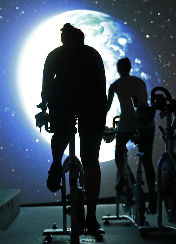 In this Jan. 3, 2017 photo, students pedal toward an image of the earth as seen from outer space in a spinning class at Brooklyn's IMAXShift in New York. Participants pedal on stationary bicycles as images flash by on a giant IMAX screen in a theatre-like setting. Stunning visuals of the solar system, soaring aerial shots of the world's major cities, scenic coastlines, mountain ranges all flash by as students spin to the beat while music-reactive visuals timed to the instructor's choreography provide a sensory overloading experience. (AP Photo/Kathy Willens)
