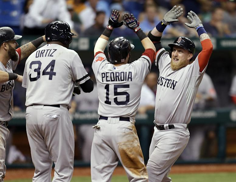 Boston Red Sox's Mike Carp, right, celebrates with teammates, from left, Mike Napoli, David Ortiz, and Dustin Pedroia after his 10th-inning grand slam off Tampa Bay Rays relief pitcher Roberto Hernandez during a baseball game Wednesday, Sept. 11, 2013, in St. Petersburg, Fla. (AP Photo/Chris O'Meara)