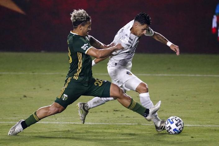 FILE - Portland Timbers defender Pablo Bonilla, left, and LA Galaxy forward Cristian Pavon vie for the ball during the second half of an MLS soccer match in Carson, Calif., in this Wednesday, Oct. 7, 2020, file photo. Major League Soccer has extended its deadline for negotiating adjustments to the existing collective bargaining agreement until Feb. 4 and warned it is prepared to lock out players if a deal isn't reached by then. (AP Photo/Ringo H.W. Chiu, File)