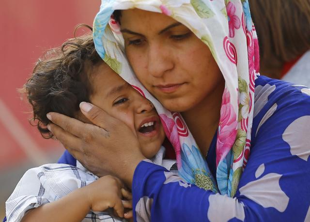 A Syrian Kurdish refugee woman and her child wait after crossing the Turkish-Syrian border near the southeastern town of Suruc in Sanliurfa province September 27, 2014. Turkish troops could be used to help set up a secure zone in Syria, if there was an international agreement to establish such a haven for refugees fleeing Islamic State fighters, President Tayyip Erdogan said in comments published on Saturday. Militants still held their positions around 10 kilometres west of Kobane inside Syria, the Reuters witness said, with Kurdish positions the last line of defence between the fighters and the town. Kobane sits on a road linking north and northwestern Syria and Kurdish control of the town has prevented Islamic State fighters from consolidating their gains, although their advance has caused more than 150,000 Kurds to flee to Turkey since last week. REUTERS/Murad Sezer (TURKEY - Tags: POLITICS CIVIL UNREST CONFLICT SOCIETY IMMIGRATION TPX IMAGES OF THE DAY)