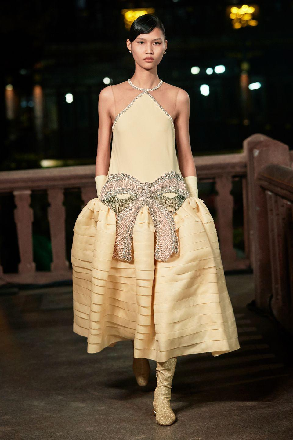 <p>Escapism played a major role in Bruno Sialelli's spring 2021 collection. Not only did the designer present at Shanghai's Yu Garden, a picturesque national landmark built in the 16th century, he also highlighted the prevalent styles of the 1920s—the decade of razzle dazzle. This journey to the past, however, was just the starting point; he took the motifs from the venue (exuberant floral prints and interplay of bright and dark colors) and the time period (drop waists, flutter sleeves, and the decorative signatures of furniture designers Armand Albert Rateau and Jean Dunand) and made them new. Think: Tiered, hoop skirts and opera coats with shawl collars paired with flat leather or sequined boots; and embroidered silk chiffon dresses.—<em>Barry Samaha</em></p>