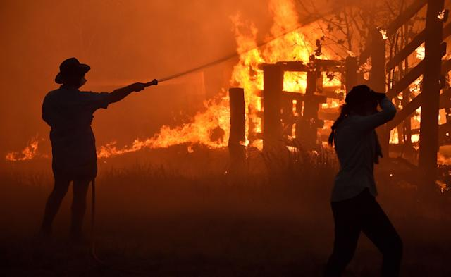 "Residents defend a property from a bushfire at Hillsville near Taree, 350km north of Sydney on November 12, 2019. - A state of emergency was declared on November 11 and residents in the Sydney area were warned of ""catastrophic"" fire danger as Australia prepared for a fresh wave of deadly bushfires that have ravaged the drought-stricken east of the country. (Photo by PETER PARKS/AFP via Getty Images)"