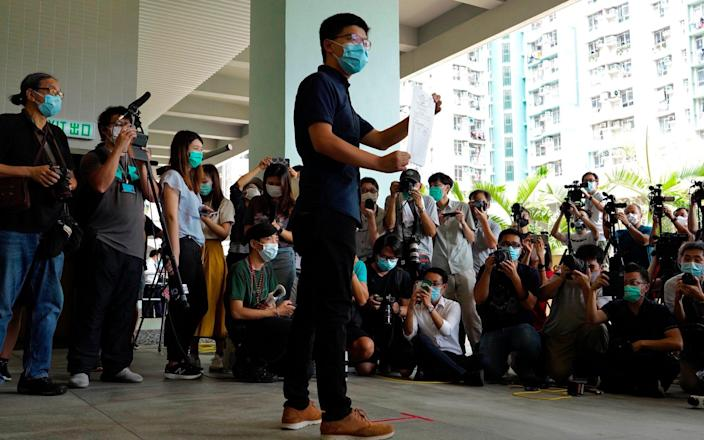 Hong Kong pro-democracy activist Joshua Wong poses with the nomination papers as he files for his candidacy in the Legislative Council elections in September - AP Photo/Vincent Yu