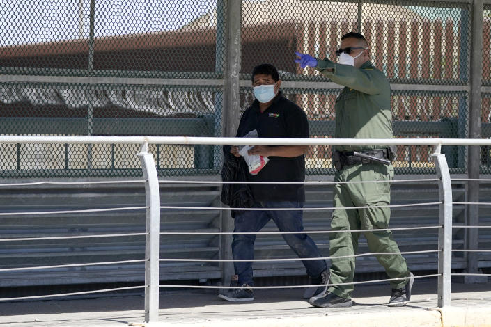 A U.S. Customs and Border Protection agent, right, leads a migrant, who was caught Thursday, March 18, 2021, in Hidalgo, Texas, trying to cross into the U.S., across the McAllen-Hidalgo International Bridge point of entry while being deported to Reynosa, Mexico. (AP Photo/Julio Cortez)