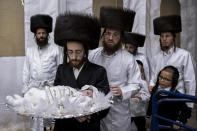 """Yaakov Tabersky, carries his 30-day-old son Yossef, the great grandchild of the chief rabbi of the Lelov Hassidic dynasty, during the """"Pidyon Haben"""" ceremony in Beit Shemesh, Israel, Thursday, Sept. 16, 2021. The Pidyon Haben, or redemption of the firstborn son, is a Jewish ceremony hearkening back to the biblical exodus from Egypt. (AP Photo/Oded Balilty)"""