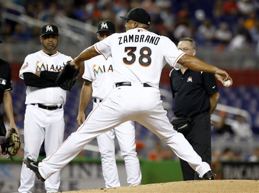 Miami Marlins manager Ozzie Guillen, left, watches his starting pitcher Carlos Zambrano (38) pitches after he was hit in the hand by a fly ball during the first inning of a baseball game in Miami, Monday, July 16, 2012 against the Washington Nationals. (AP Photo/J Pat Carter)