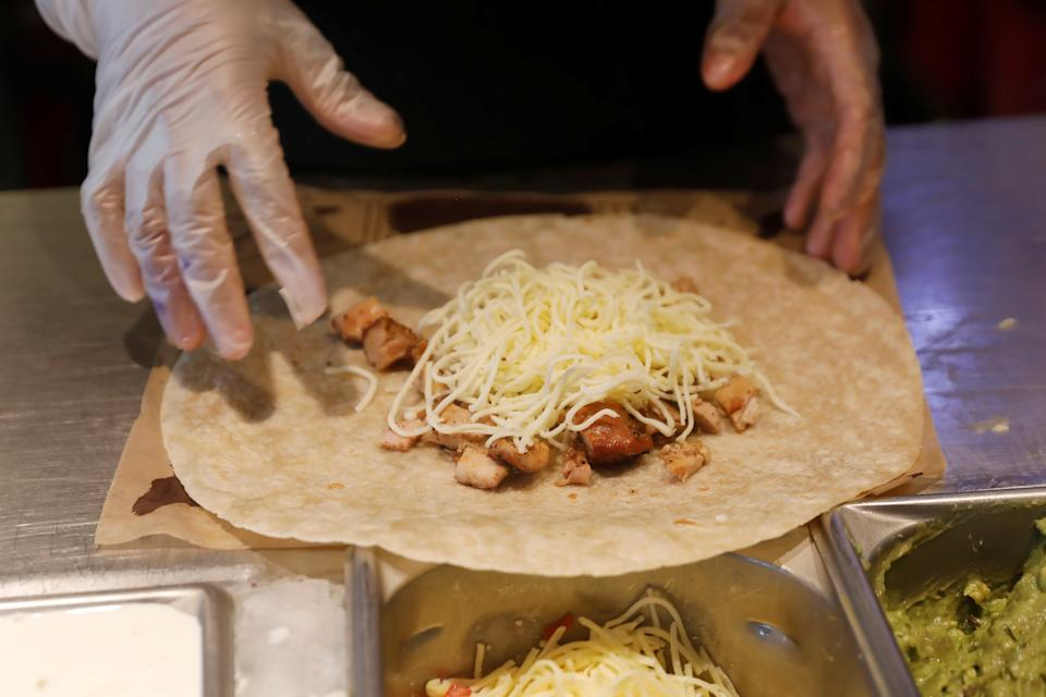 A Chipotle worker makes the new Quesadilla dish at the Chipotle Next Kitchen in Manhattan, New York, U.S., June 28, 2018.  REUTERS/Shannon Stapleton