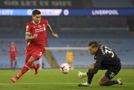 Liverpool's Roberto Firmino tries to get past Manchester City's goalkeeper Ederson during the English Premier League soccer match between Manchester City and Liverpool at the Etihad stadium in Manchester, England, Sunday, Nov. 8, 2020. (Shaun Botterill/Pool via AP)