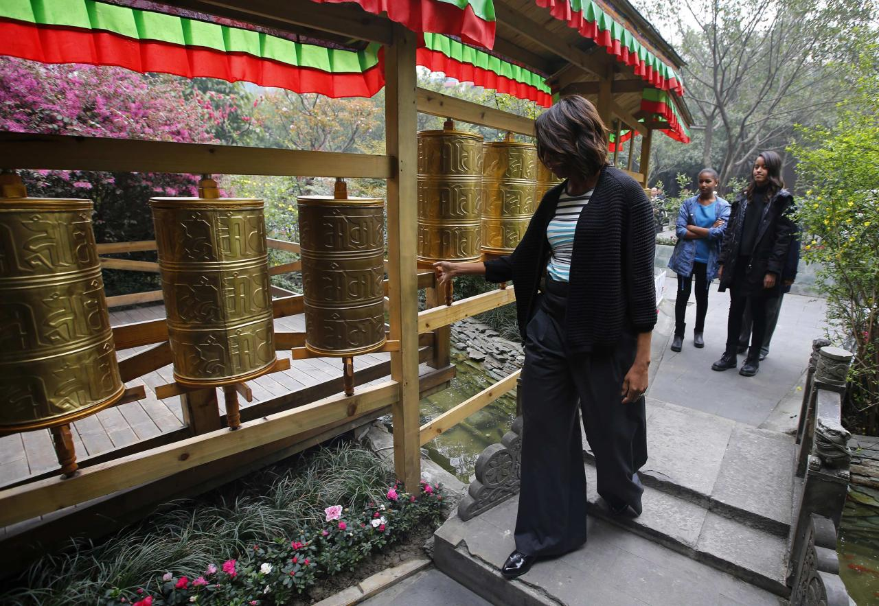 U.S. first lady Michelle Obama (L) touches Tibetan prayer wheels as her daughters Malia (R) and Sasha watch, outside a Tibetan restaurant in Chengdu, Sichuan province, March 26, 2014. REUTERS/Petar Kujundzic (CHINA - Tags: POLITICS RELIGION)