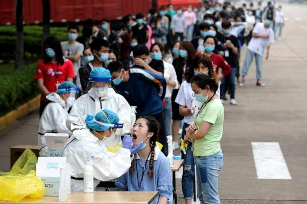 PHOTO: People line up for medical workers to take swabs to test for COVID-19 at a large factory in Wuhan in central China's Hubei province on May 15, 2020. (AP)