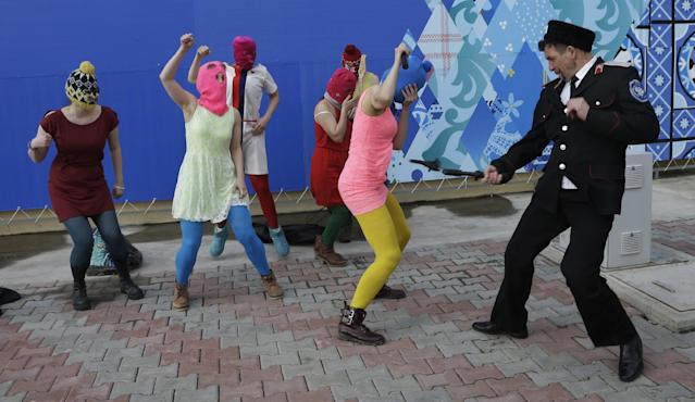 A Cossack militiaman attacks Nadezhda Tolokonnikova as she and fellow members of the punk group Pussy Riot, including Maria Alekhina, center, in the pink balaclava, stage a protest performance in Sochi, Russia, on Wednesday, Feb. 19, 2014. The group had gathered in a downtown Sochi restaurant, about 30km (21miles) from where the Winter Olympics are being held. They ran out of the restaurant wearing brightly colored clothes and ski masks and were set upon by about a dozen Cossacks, who are used by police authorities in Russia to patrol the streets