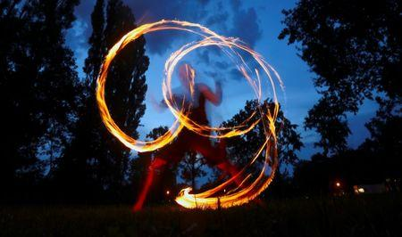 A man performs with fire at Friedrichshain Park in Berlin, Germany, August 28, 2016. Berlin is home to many performers, who put on their shows at bars, clubs and other venues. REUTERS/Hannibal Hanschke