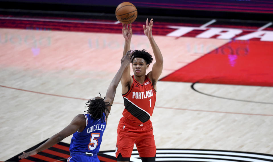 Portland Trail Blazers guard Anfernee Simons, right, hits a shot over New York Knicks guard Immanuel Quickley, left, during the first half of an NBA basketball game in Portland, Ore., Sunday, Jan. 24, 2021. (AP Photo/Steve Dykes)