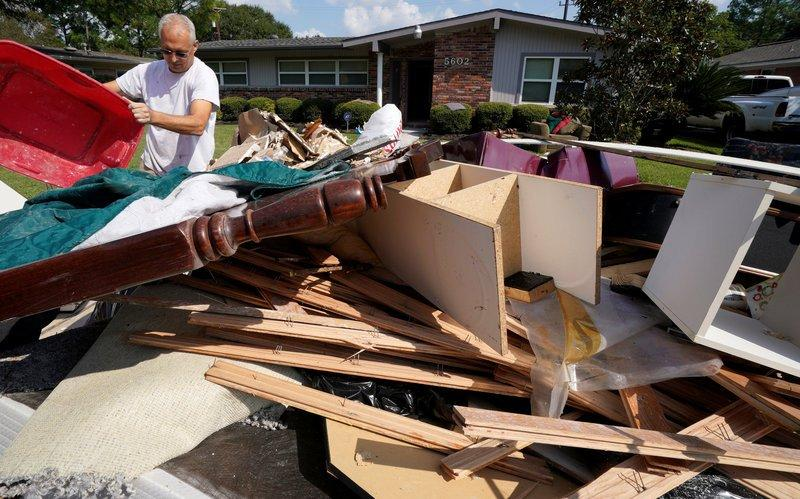 A homeowner adds to a trash pile of Hurricane Harvey flood damage in southwestern Houston, Texas, U.S. September 2, 2017. REUTERS/Rick Wilking