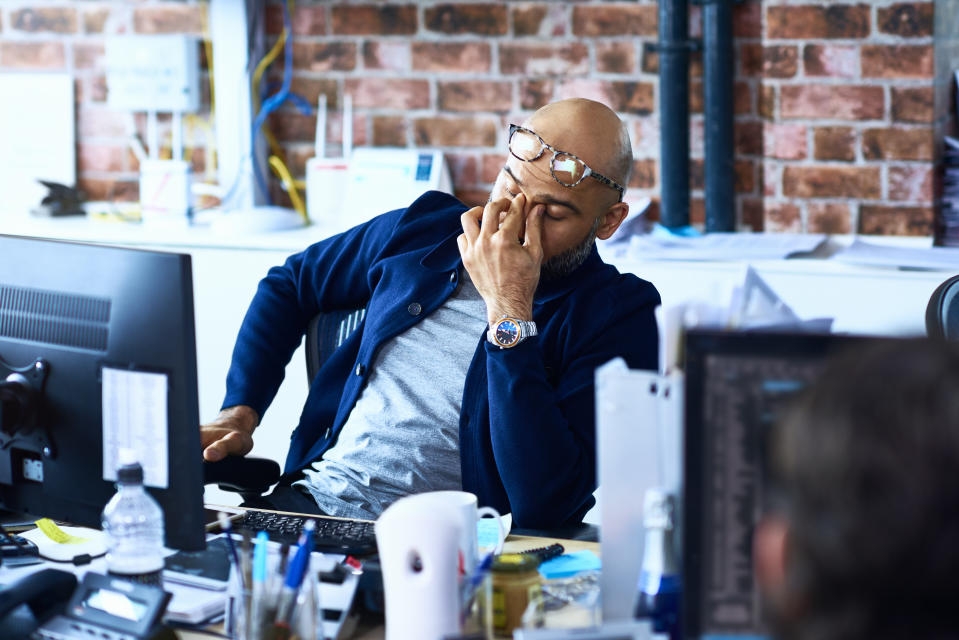 Tired man sitting at desk in modern office