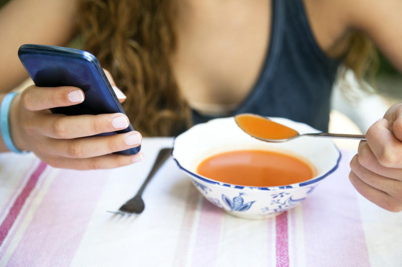 Teenager chatting with the mobile phone while having lunch.