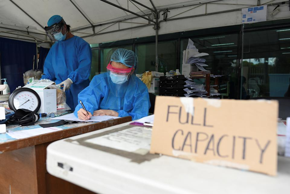 FILE PHOTO: Health workers sort patients' files at a triage area in Santa Ana Hospital, where a sign indicating that the hospital's coronavirus disease (COVID-19) facility is at full capacity is displayed, April 9, 2021. (Source: REUTERS/Lisa Marie David)
